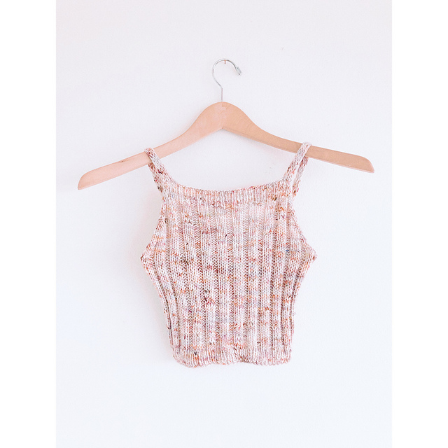 a handknit cropped tank top in a peach color, made with 2 by 2 rib, hanging on a wooden hanger in front of a white background